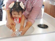 Réflexion de miroir d'une petite fille, avec l'aide de sa mère, apprenant à se laver les mains avant un repas photos libres de droits