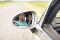 Réflexion de miroir latérale des couples heureux conduisant la voiture Photo stock