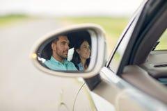 Réflexion de miroir latérale des couples heureux conduisant la voiture Photographie stock