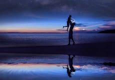 Réflexion de miroir de père et de fille de silhouette sur la plage avec million de début de la matinée de galaxie d'étoiles et de images stock
