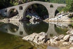 Réflexion de pont du ` s de diable en rivière d'Arda et montagne de Rhodopes, Bulgarie Photos stock