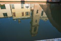 Réflexion de tour et de maison dans le canal de Comacchio, Italie images stock