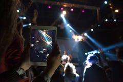 Réflexion des effets de la lumière au téléphone portable à un concert (Gadge photographie stock