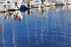 Réflexion des mâts dans l'eau bleue Photos stock