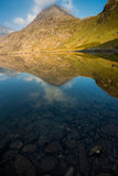 Réflexion des montagnes avec des pierres dans le premier plan Photos stock