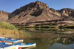 Réflexion des montagnes rocheuses et des canoës sur la rivière orange en Namibie photo libre de droits