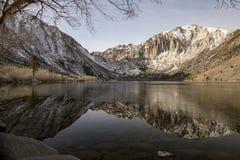 Réflexion des montagnes sur un lac glacial vitreux en hiver photographie stock libre de droits