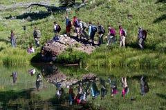 Réflexion des randonneurs dans le lac images libres de droits