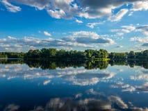 Réflexion du ciel nuageux dans l'eau de peu de lac photographie stock