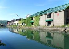 Réflexion du vieil entrepôt le long du canal d'Otaru avec une mouette de vol Images libres de droits