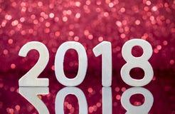 Réflexion en bois de nombres de la nouvelle année 2018 sur la table en verre Photos stock