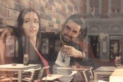 Réflexion se reposante de fenêtre de boutique de caffee d'homme de jeune femme image stock