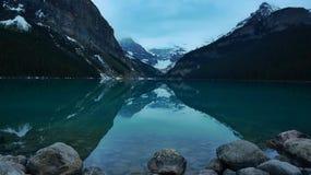 Réflexion sur l'eau immobile de Lake Louise Photographie stock