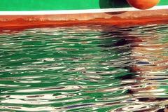 Réflexions colorées de bateau sur l'eau onduleuse Photos libres de droits
