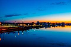 Réflexions de coucher du soleil au-dessus de ville et de rivière image stock
