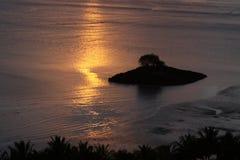 Réflexions de lever de soleil au-dessus d'une île tropicale Images libres de droits