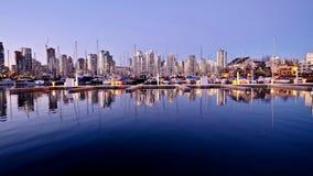 Réflexions des lumières et des bateaux de ville dans l'eau calme Image libre de droits