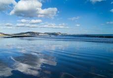 Réflexions des nuages sur la plage chez Lyme REGIS, Dorset Image stock