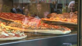 Réflexions des personnes marchant par une pizzeria banque de vidéos