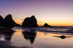 Réflexions des roches géantes dans le sable humide images stock