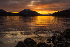 Réflexions oranges de coucher du soleil sur un lac avec des montagnes et un ciel nuageux Images libres de droits