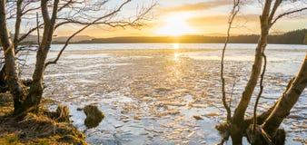 Réflexions oranges de coucher du soleil sur un lac avec des montagnes et un ciel nuageux photographie stock libre de droits