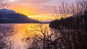 Réflexions oranges de coucher du soleil sur un lac avec des montagnes et un ciel nuageux Photo libre de droits