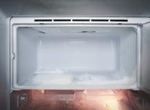 Réfrigérateur avec de la glace congelée dans le réfrigérateur image stock