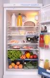 Réfrigérateur complètement avec quelques genres de nourriture Photos libres de droits
