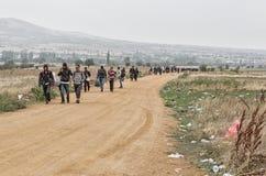 Réfugiés et migrants marchant la route poussiéreuse sous la pluie au Photos libres de droits