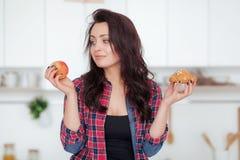 Régime Concept suivant un régime Nourriture saine Belle jeune femme choisissant entre les fruits et les bonbons Perte de poids photographie stock libre de droits