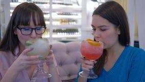 Régime délicieux, filles heureuses appréciant le jus de fruit sain de vitamine de grands verres à l'intérieur de restaurant banque de vidéos