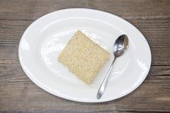 Régime de Dukan Gâteau délicieux frais de régime au régime de Dukan d'un plat de porcelaine avec une cuillère sur un fond en bois Photographie stock