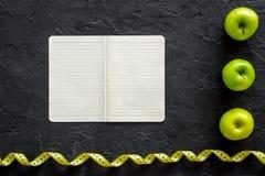 Régime de la laiterie de régime Carnet, pommes et bande de mesure sur la maquette noire de vue supérieure de fond Photographie stock libre de droits