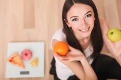 Régime et concept d'aliments de préparation rapide Femme de poids excessif se tenant sur la balance tenant la pizza Nourriture in images stock