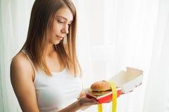 Régime Femme avec sentiment coupable pour manger un hamburger images libres de droits