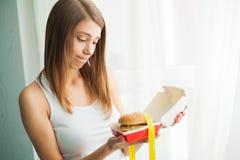 Régime Femme avec sentiment coupable pour manger un hamburger image stock