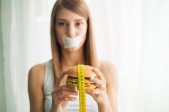 Régime Jeune femme avec le ruban adhésif au-dessus de sa bouche, l'empêchant pour manger de la nourriture industrielle Concept sa image stock