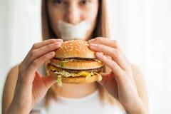 Régime Jeune femme avec le ruban adhésif au-dessus de sa bouche, l'empêchant pour manger de la nourriture industrielle Concept sa image libre de droits