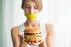 Régime Jeune femme avec le ruban adhésif au-dessus de sa bouche, l'empêchant pour manger de la nourriture industrielle Concept sa photo stock