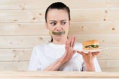Régime La femme de portrait veut manger un hamburger mais la bouche coincée de skochem, le concept du régime, la nourriture indus photographie stock
