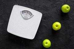 Régime pour le poids perdant Échelle et pommes de salle de bains sur la vue supérieure de fond noir images stock