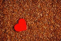 Régime sain Lin oléagineux de graines de lin comme fond de nourriture et coeur rouge photographie stock libre de droits