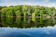 Région boisée, réflexions de lac et ondulations au Shropshire, R-U image stock