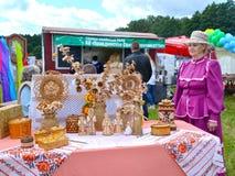 Région de Kaliningrad, Russie La dame pluse âgé vend des produits d'écorce de bouleau à une foire de l'art populaire photographie stock libre de droits