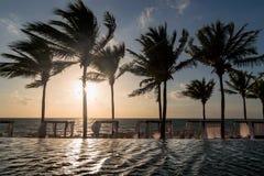 Région de salon d'une station de vacances mexicaine à extrémité élevé avec une piscine d'infini donnant sur l'océan au lever de s images libres de droits