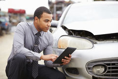 Régleur de perte utilisant la Tablette de Digital dans l'inspection d'épave de voiture photo stock