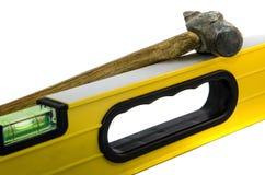 Régua amarela da construção com um martelo em um fundo branco fotografia de stock