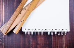 Régua e caderno de madeira na placa de madeira Imagens de Stock