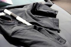 R?gulateur du trafic de baguette magique et veste de moto de femmes de couleur sur le capot de la voiture Montre Moto photos stock